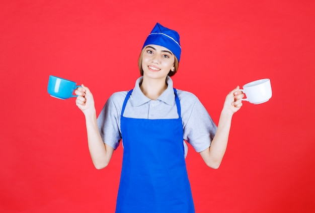 Female barista holding blue and white big cups