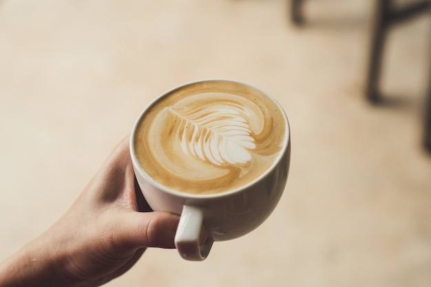 Female barista holding latte art coffee