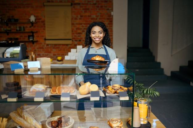 Женщина-бариста в фартуке держит тарелку с круассаном в кафе