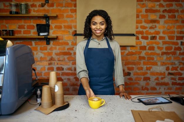Женский бариста в фартуке готовит ароматный кофе в кафе. женщина делает свежий эспрессо в кафетерии, официант за стойкой в баре