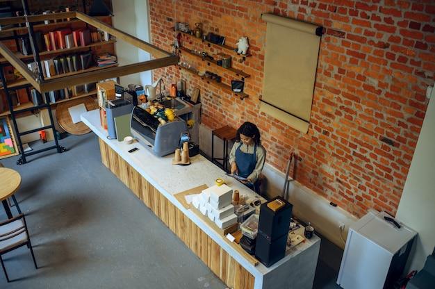 エプロンの女性バリスタがカフェで注文。女性はカフェテリアで新鮮なエスプレッソを作り、ウェイターはバーのカウンターでコーヒーを準備します、上面図