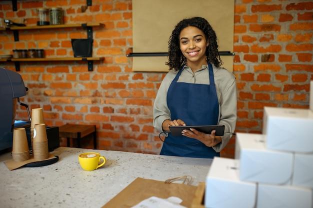 Женский бариста в фартуке принимает заказы в кафе. женщина готовит свежий эспрессо в кафетерии, официант готовит кофе на стойке в баре