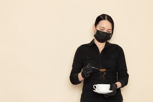 白い壁に黒い滅菌マスクでコーヒーブラウン乾燥茶機器成分と黒いシャツズボンの女性バリスタ