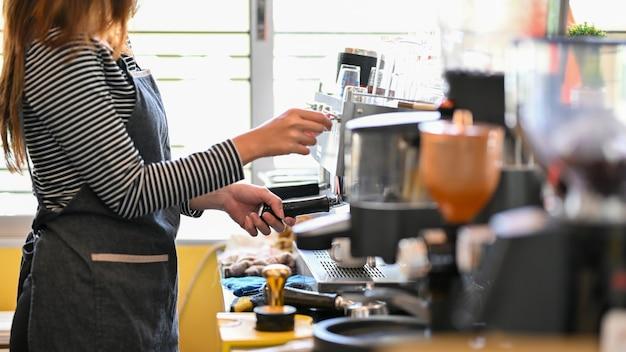 顧客がコーヒーを淹れるためにおいしいコーヒーを準備するコーヒーマシンでコーヒーを作る女性のバリスタ