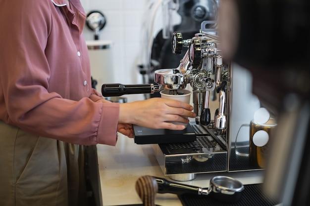 コーヒーマシンでコーヒーを作る女性バリスタ