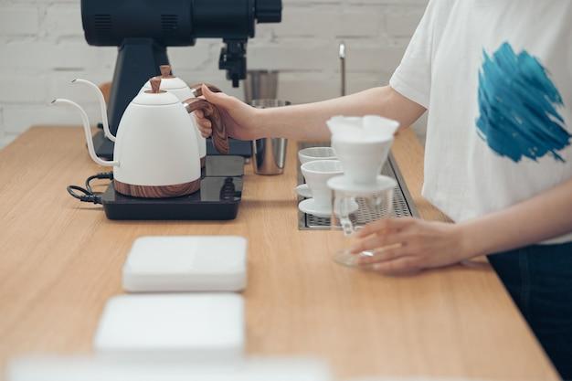 카페테리아에서 필터 커피를 만드는 여성 바리스타