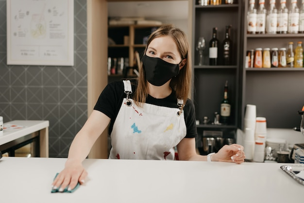 A female barista in a medical black face mask smiles and cleaning the bar counter in a coffee shop. a pretty waitress disinfecting a cafe.