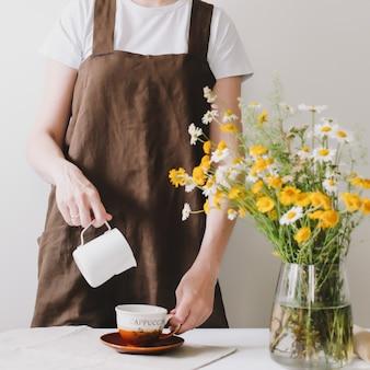 コーヒーカップにミルクを注いで、コーヒーを作る女性バリスタ