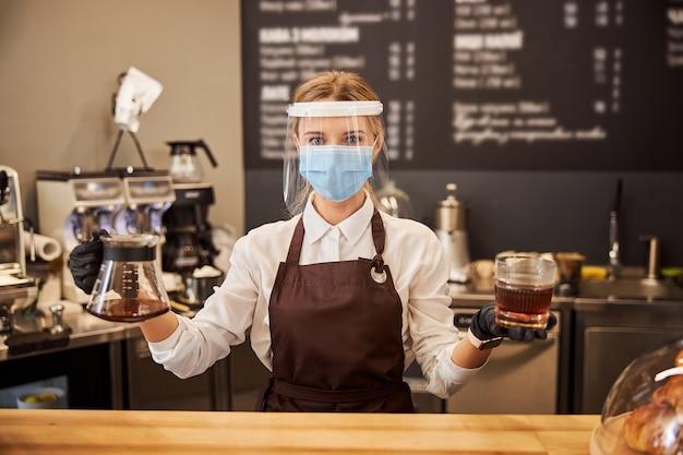 커피 바 손님을 위해 에스프레소를 준비하는 여성 바리스타