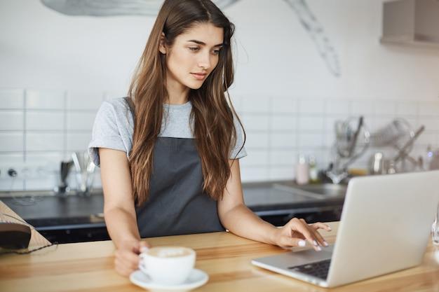 ラップトップでウェブとソーシャルメディアをサーフィンする小さな休憩を持っている彼女のコーヒービジネスを実行している女性のバリスタ。