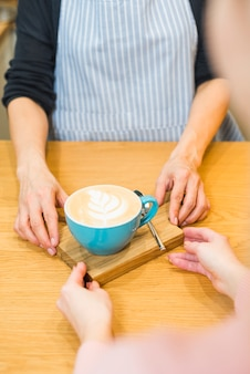 Female barista serving cup of coffee latte on wooden chopping board