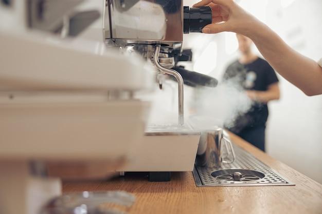 Женский бариста с помощью кофемашины в кафетерии