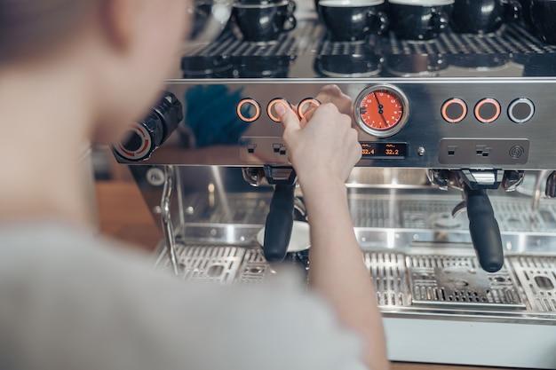 카페테리아에서 현대적인 커피 머신을 사용하는 여성 바리스타