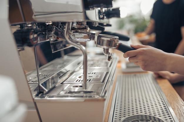Женский бариста, использующий профессиональную кофеварку в кафе