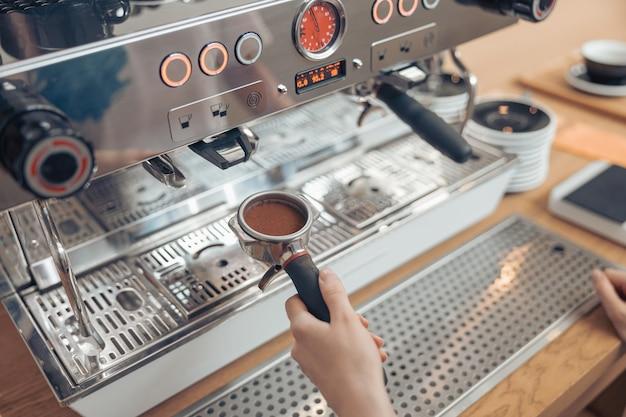 Женщина-бариста, использующая профессиональную кофемашину в кафетерии