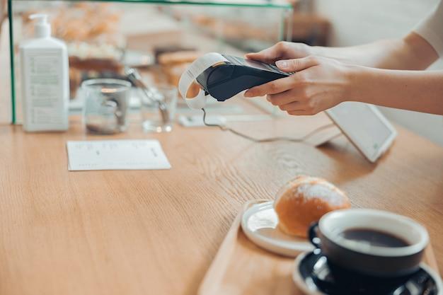식당에서 비접촉 결제를 위해 단말기를 사용하는 여성 바리스타