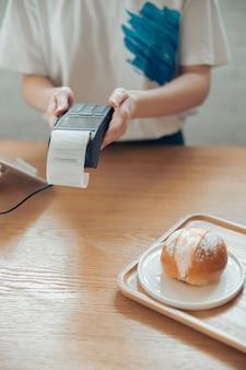 커피숍에서 비접촉 결제를 위해 단말기를 사용하는 여성 바리스타