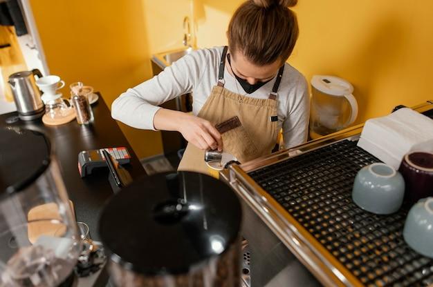 Женский бариста с маской, работающей в кофейне
