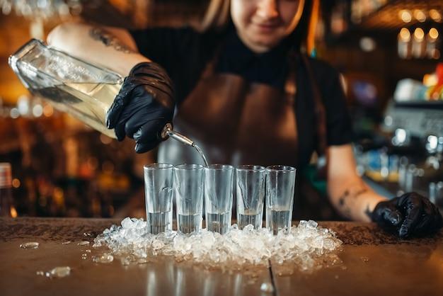Бармен женщина в перчатках ставит напитки на лед