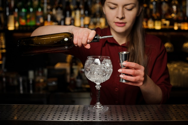 Female barman pouring bitter for making an aperol syringe cocktail