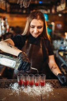 Женщина-бармен наливает напиток в стакан