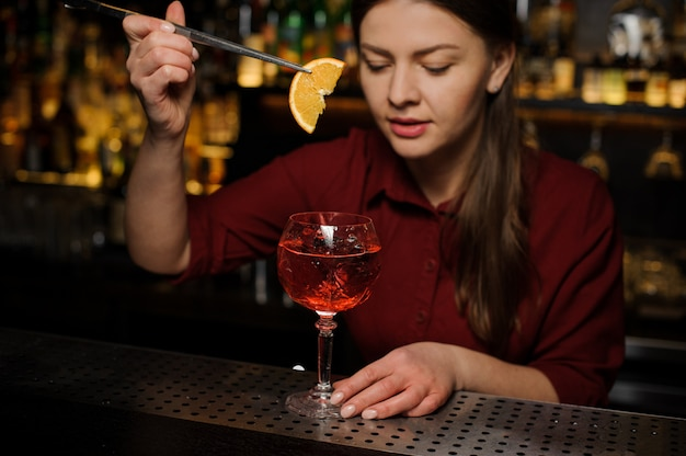Female barman putting a slice of orange into a glass of aperol syringe cocktail