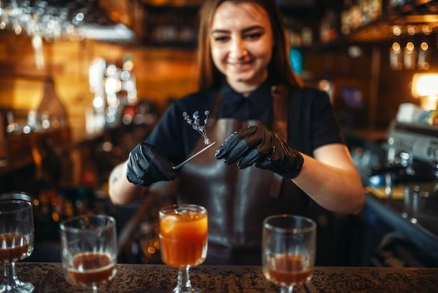 Бармен женщина держит стакан с коктейлем