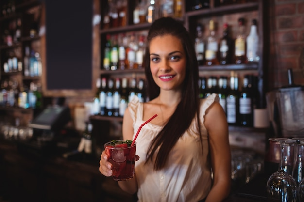 Female bartender holding a cocktail drink at bar counter