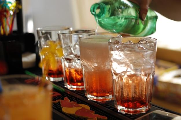 Женский бармен делает коктейль с добавлением соды