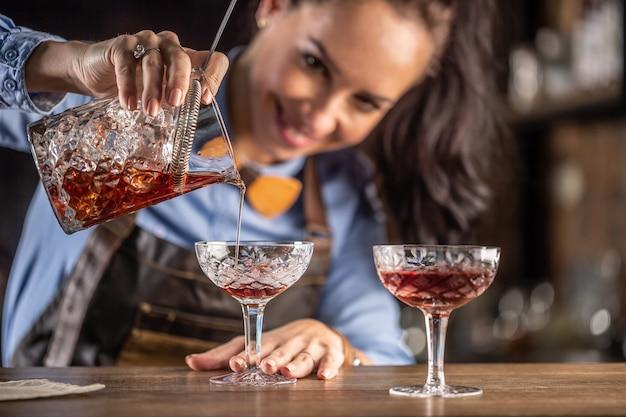 Female bartender pours manhattan cocktail into an ornamental glass.