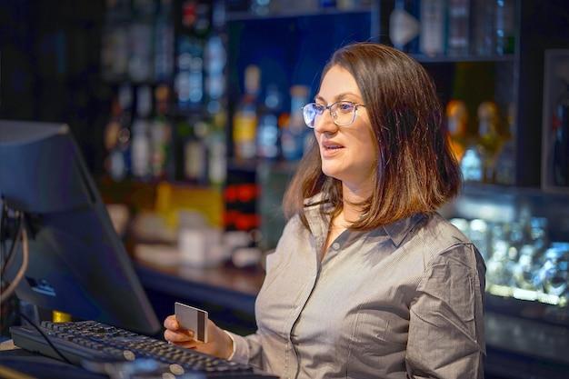 금전 등록기로 새 주문을 등록하는 여성 바텐더. 금전 등록기로 새로운 주문을 등록하는 식당 직원