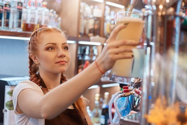 Женщина-бармен разливает пиво в баре