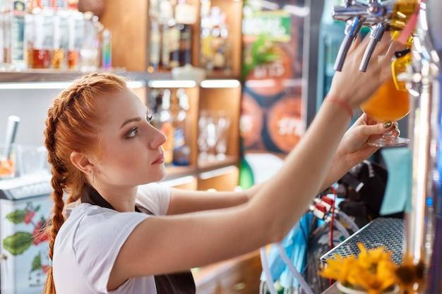 Женщина-бармен разливает крафтовое пиво в баре
