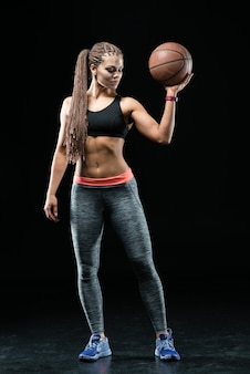 Female basketball player - isolated over a black background