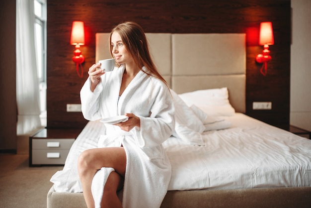 Female in bathrobe holds in hand a cup of coffee