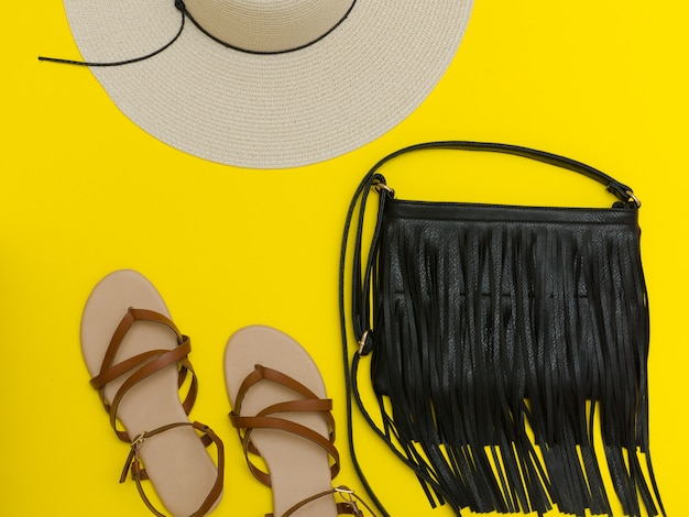 Female beach hat, handbag, sandals on yellow