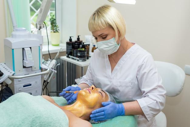 Женский косметолог делает пациенту золотую маску в салоне