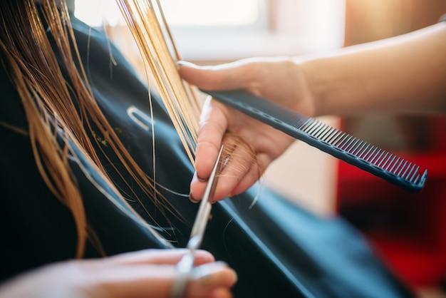 女性美容師が美容院でくしをしている女性。ビューティーサロンでのヘアスタイル作り