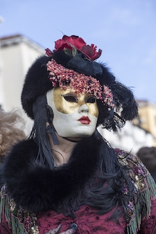 Female in a beautiful dress and traditional venice mask during the world-famous carnival