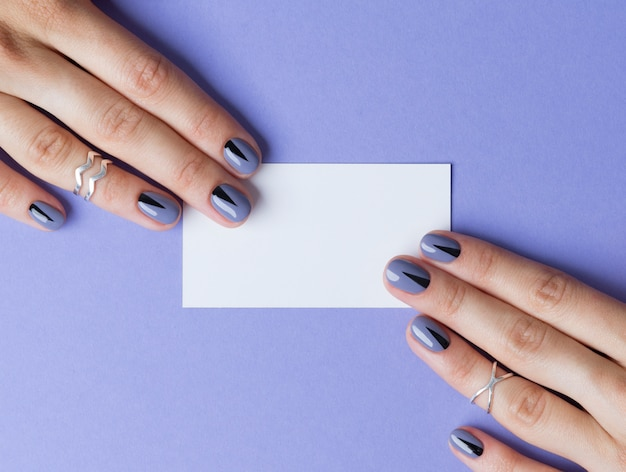 Female beautiful manicured hands with blank business card