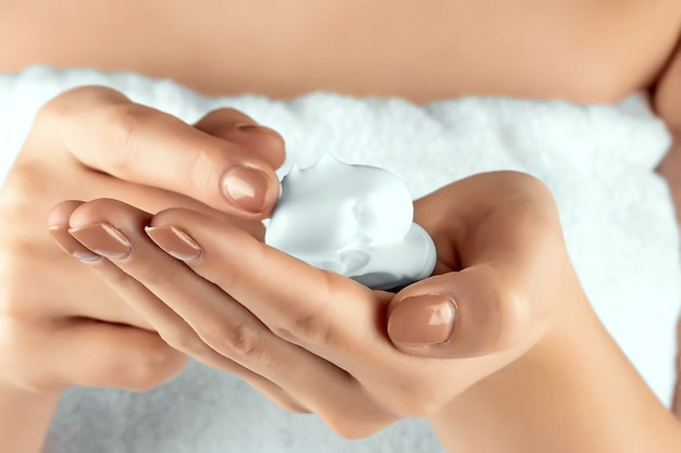 Female beautiful well-groomed hands with shaving foam close-up. body care, personal hygiene, female beauty.