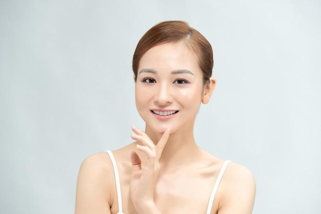 Концепция женской красоты. жизнерадостная девушка с обнаженным макияжем и идеальной кожей, улыбаясь, стоя на белом фоне.