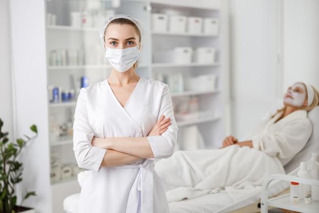 美容クリニックでは、女性の美容医師がフェイスマスクを着用し、クリームやマスクで背景に忍耐強く横たわっています。