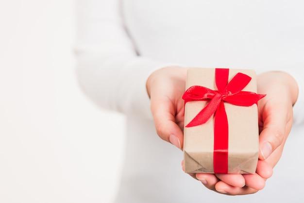 Руки женской красоты держат маленькую подарочную коробку, обернутую бумагой с лентой