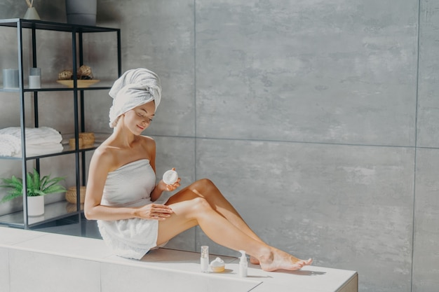 Female beauty and skin care concept. young pretty woman applies cream, has slender legs, makes cosmetological procedure, wrapped in towel, feels perfect, takes care of her body and appearance