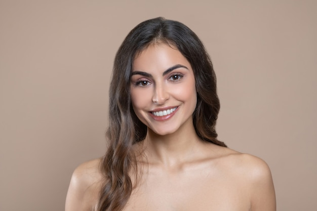Female beauty. smiling beautiful young adult woman with bare shoulders in great mood on light background
