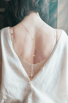 Female in beige lacy bra and open back blouse, fashion