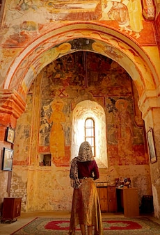 Женщина впечатлена средневековыми фресками внутри церкви монастыря герати кутаиси грузия