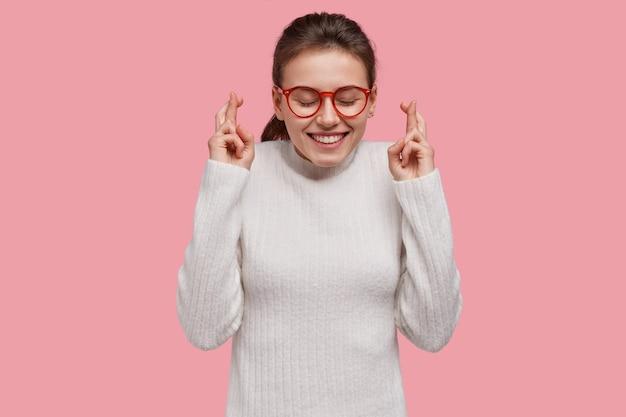 Верующая женщина имеет верное оптимистическое выражение лица, держит пальцы скрещенными, ждет чуда или мечты