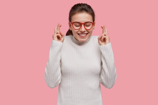 La donna credente ha un'espressione fedele e ottimista, incrocia le dita, aspetta il miracolo oi sogni che si avverano
